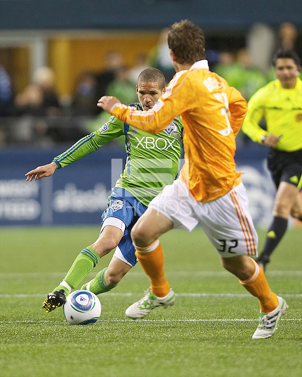 Seattle Sounders FC midfielder Osvaldo Alonso  changes directions against Houston Dynamo defender Bobby Boswell during play at Qwest Field in Seattle Friday March 25, 2011. The match ended in a 1-1 draw.