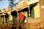 Lolgorian, Kenya. Visiting tourist man wearing a traditional red Maasai shukka in front of a row of local shops.