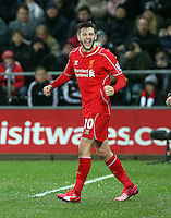 SWANSEA, WALES - MARCH 16: Adam Lallana celebrates the goal scored by team captain Jordan Henderson of Liverpool goal during the Premier League match between Swansea City and Liverpool at the Liberty Stadium on March 16, 2015 in Swansea, Wales