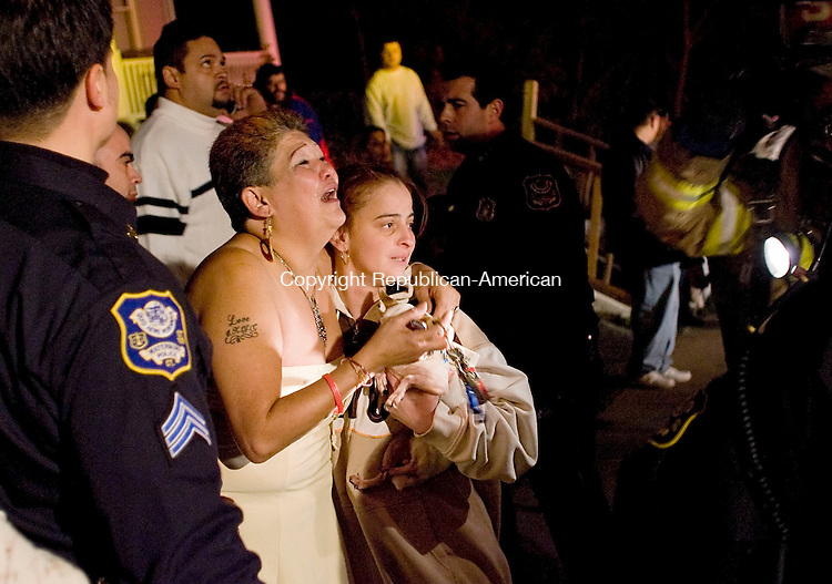 WATERBURY, CT--03 November 07--110307TJ07 - Ida Colon, center left, who lives at 46 Silver Street in Waterbury, Conn., is comforted by Jackalene Santiago as she watches Waterbury firefighters battle a fire in her home on Saturday, November 3, 2007. T.J. Kirkpatrick/Republican-American