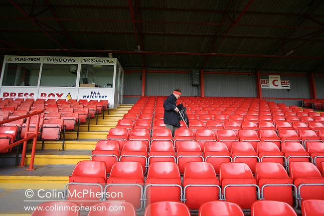 A member of the groundstaff picking up litter at Morecambe Football Club's Christie Park. The club was preparing for the club's first-ever season in the Football League having been promoted from the Conference the previous season.