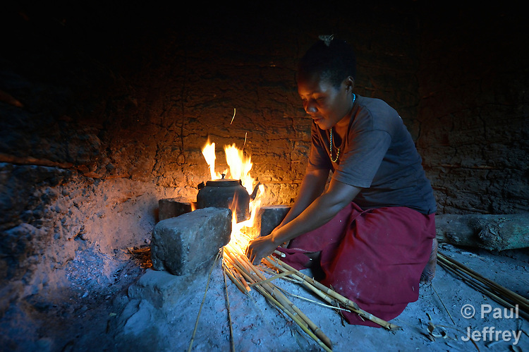 Sylvia Namaganda starts a fire to make tea in the predawn darkness in Lukaya, Uganda, where the Good Samaritan Women's Project has helped rural women improve their financial literacy, thus improving the quality of life for the women, many of whom are widows who also care for children who lost their parents to AIDS. The program was funded by the Call to Prayer and Self-Denial of United Methodist Women. Namaganda, a widow, cares for her own three children along with four she adopted after her sister died.