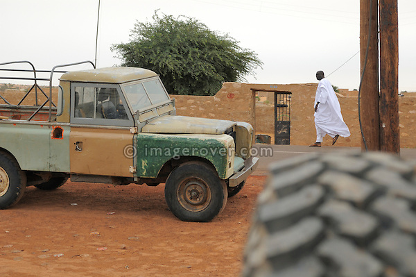 Africa, Mauritania, Sahara Desert, Tidjikdja. Black mauritanian man wearing a traditional white dress passing an old working Land Rover Series 3 Truck Cab at. --- No releases available. Automotive trademarks are the property of the trademark holder, authorization may be needed for some uses.