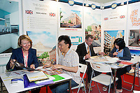 Alice Macdonald of Knight Knox International Ltd, speaks to a potential buyer as Alisdair and Eva Leong sign papers in the background at their booth at the Smart International Property Investment Expo at the Hong Kong Convention and Exhibition Centre in Hong Kong. <br /> 07-08 June, 2014<br /> <br /> Photo by Tim O'Rourke / Sinopix