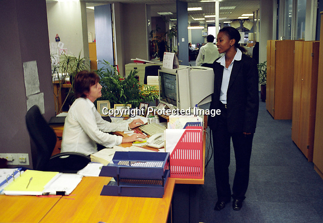 dibucor00097 Business Cooperate Empowerment, black, office, workplace, power, woman.Phumzile Langeni, a stock broker, talks to her white secretary in their office at Bernard Jacobs Mellet (BJM) stock brokers in Rosebank, Johannesburg, South Africa..©Per-Anders Pettersson/iArika Photos