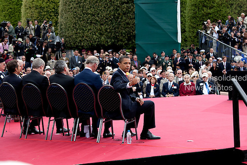 """Colleville-sur-Mer, France - June 6, 2009 -- United States President Barack Obama gives a """"thumbs-up"""" to a group of WW II veterans sitting behind him on stage prior to speaking during the 65th anniversary of the D-Day invasion in Normandy, France, Saturday, June 6, 2009. .Mandatory Credit: Pete Souza - White House via CNP"""