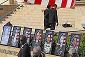 Fort Hood, TX - November 10, 2009 -- President Barack Obama and his wife First Lady Michelle Obama pass photos fo the fallen as they depart from the memorial service for the 12 soldiers and one civilian killed at Fort Hood U.S Army Post near Killeen, Texas, USA 10 November 2009. Army Major Malik Nadal Hasan reportedly shot and killed 13 people, 12 soldiers and one civilian, and wounded 30 others in a rampage 05 November at the base's Soldier Readiness Center where deploying and returning soldiers undergo medical screenings.  .Credit: Tannen Maury / Pool via CNP