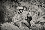 A miner hammers a hole in the wall to plant dynamite in a silver mine in Potosi, Bolivia...