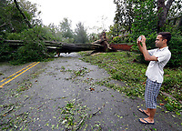 Shane Fernando takes a photo of fallen trees near his home in Wilmington, N.C., after Hurricane Florence made landfall Friday, Sept. 14, 2018. (AP Photo/Chuck Burton)