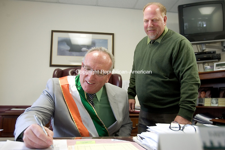 WOLCOTT CT. 17 March 2015-031715SV10-From left, Chuck O'Neil of Wolcott was named Irish Mayor for the Day by Mayor Tom Dunn at Town Hall in Wolcott Tuesday. O&rsquo;Neil was recently inducted into the Wolcott Circle of Sports Hall of Fame and is a past president of the Wolcott Land Conservation Trust, a former coach for A League of Their Own girls&rsquo; softball and a former Wolcott junior basketball coach. He currently helps coordinate the town&rsquo;s summer and fall basketball programs. O'Neil signs official documents in the Mayor&rsquo;s office. <br /> Steven Valenti Republican-American