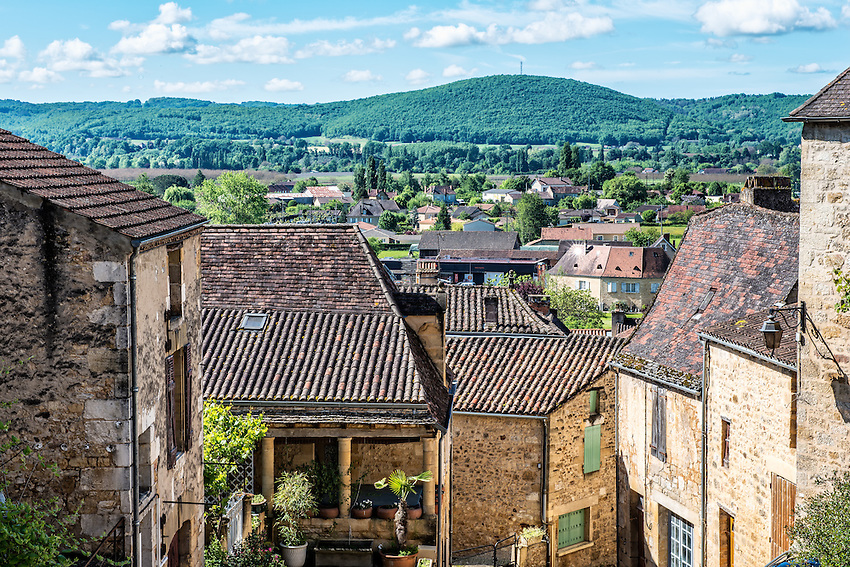 A rural landscape is visible beyond the rooftops of the village of Saint-Cyprien in the Périgord region of France.
