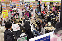 People are siting and relaxing on massage chairs at a big electric shop, LABI in shinjuku