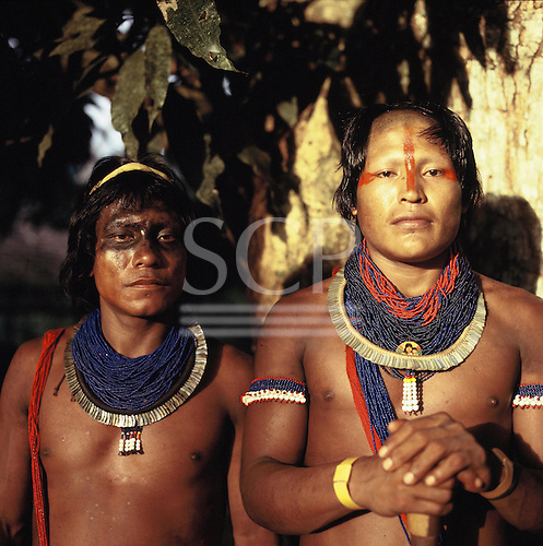 Xingu, Brazil. Two young Kayapo men wearing blue beads, shell necklaces and urucum and genipapo face paint.