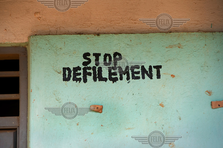 Slogan saying 'Stop defilement' painted on a school wall.