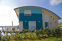 Europe, NLD, the Netherlands, Gelderland, Maasbommel, a pre-operating study of the Dura Vermeer Group: flood protected amphibian homes at the river Meuse <The houses have a watertight cellar like a tub made of concrete. They are mounted at two steel pylons to prevent them against leeways and can lift with the rising waters. The buildings follow an increase of the water level up to 5,5 meters.>....Europa, NLD, Niederlande, Gelderland, Maasbommel, ein Pilotprojekt der Dura Vermeer Group: hochwassersichere Amphibienhaeuser an der Maas <Die Haeuser besitzen einen wasserdichten Keller aus Beton, der wie eine schwimmfaehige Wanne bei steigendem Wasser fuer genuegend Auftrieb sorgt. Sie sind an zwei Stahlpylonen gegen das Abdriften gesichert und folgen einem Anstieg des Wasserspiegels bis zu 5,5 Meter.>......[Copyright / Contact: Vera Schimetzek, Bornstrasse 5, 58300 Wetter, Germany, cell: 0049.(0)151.21220918, schimetzek@web.de, www.schimetzek-foto.de, publication is subject to a fee and report, the General Terms and Conditions apply. Die Veroeffentlichung ist melde- und honorarpflichtig, die AGB sind bindend.]