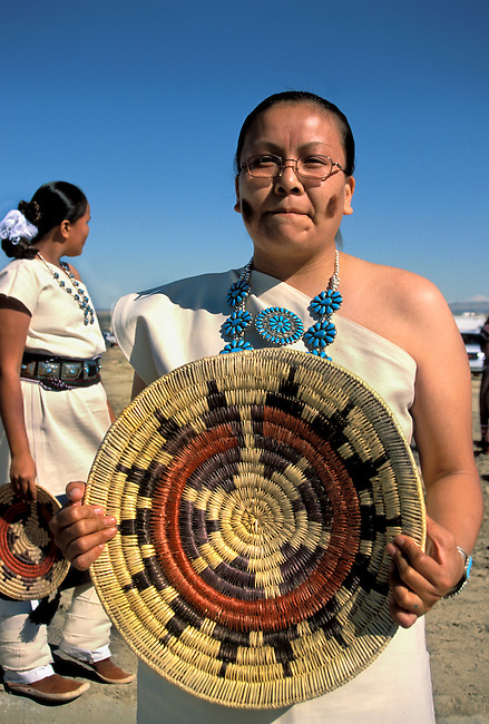 A Navajo teenager from the Rainbow Dancers is dressed in traditional cotton dress and holds a basket