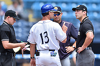 Asheville Tourists manager Warren Schaeffer (13) discusses play from the night before with first base umpire Jason Johnson as home plate umpire Sam Burch and Charleston RiverDogs hitting coach Greg Colbrunn look on before a game against the Charleston RiverDogs at McCormick Field on July 10, 2016 in Asheville, North Carolina. The Tourists defeated the RiverDogs 4-2. (Tony Farlow/Four Seam Images)