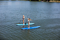 Two attractive Austin females enjoying Stand Up Paddle Boarding (SUP) - Shot on Lady Bird Lake in Austin, Texas.