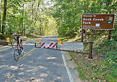 Unidentified biker rides past the barricades and sign at the entrance to Rock Creek Park in Chevy Chase, Maryland on Tuesday, October 1, 2013.  The National Park Service has closed all of its facilities due to Congress not passing a funding bill by midnight September 30.  The road, Rock Creek Parkway, which runs through the park, is a major thoroughfare for motor vehicles and bicycles between the Maryland suburbs and downtown Washington, D.C.<br /> Credit: Ron Sachs / CNP<br /> (RESTRICTION: NO New York or New Jersey Newspapers or newspapers within a 75 mile radius of New York City)