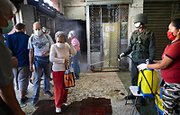An elderly woman, wearing a protective face mask is sprayed with a disinfectant bleach solution by a soldier as a preventive measure against the spread of the new coronavirus, at the entrance of a food market in Caracas, Venezuela, March 20, 2020. (AP Photo/Ariana Cubillos)