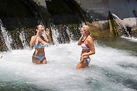 Two sexy women in bikinis enjoy the cool spring falls at the Barton Springs Spillway on a blistering triple-digit Texas summer day, Zilker Park, Austin, Texas.