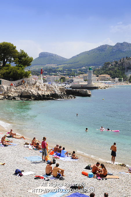 People bathing in Cote de Azur public beach. Riviera seashore in Nice, France.