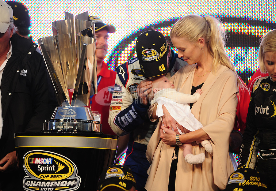 Nov. 21, 2010; Homestead, FL, USA; NASCAR Sprint Cup Series driver Jimmie Johnson kisses daughter Genevieve Marie Johnson as she is held by wife Chandra Johnson after winning his fifth consecutive NASCAR championship following the Ford 400 at Homestead Miami Speedway. Mandatory Credit: Mark J. Rebilas-