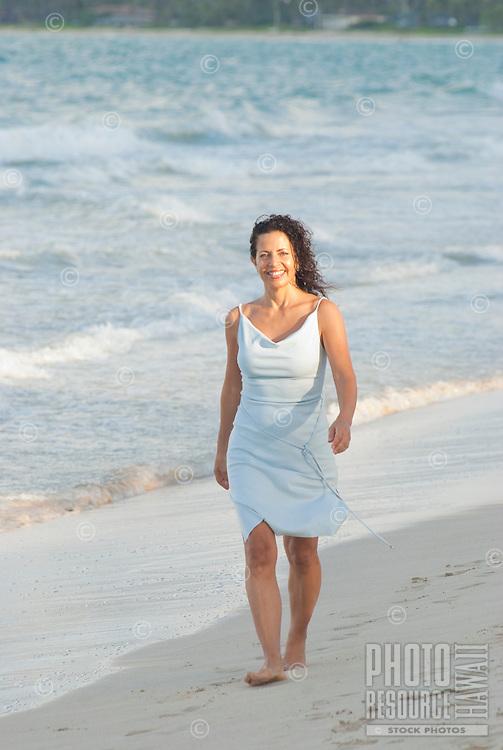 Woman walking Kailua beach with curly hair wearing soft blue dress