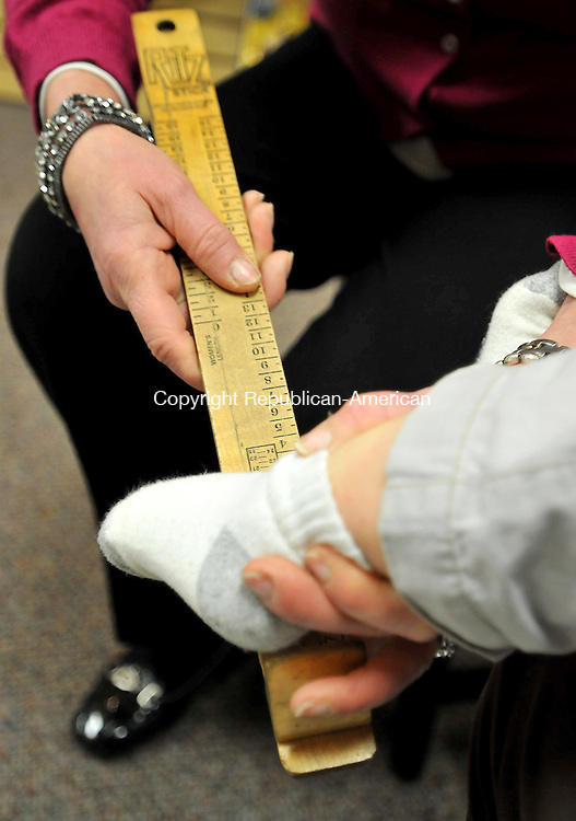 SOUTHBURY,  CT, 03 FEBRUARY  2012-020312JS09-Sheila Gillen, Manager of Wesley's Shoes in Southbury, measures the feet of 2-year old Colin Bailey on Friday as he gets fitted for a new pair of shoes. . Jim Shannon Republican-American