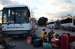 A woman waits with her children, for a bus bound for the airport in Tunis, after crossing into Tunisia at the border crossing with Libya near Ben Guerdane, Tunisia, Thursday, Feb. 24, 2011. Foreign nationals, including many Egyptian workers, fled Libya as Col. Muammar Qaddafi tried to maintain his grip on the capital Tripoli. In the latest uprising to strike the Middle East, street protests which began in Eastern Libya spread to Tripoli, as opposition members called for Qaddafi to follow Tunisian president Zine el-Abidine Ben Ali and Egyptian president Hosni Mubarak and step down.