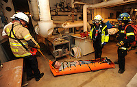 NWA Democrat-Gazette/ANDY SHUPE<br /> Mock patient Kaden Curry (center) is pulled Wednesday, Nov. 25, 2015, by emergency personnel from Fayetteville, Springdale and Rogers through a mechanical room and into a utility tunnel during a hazardous-materials and confined-space extrication drill in Kimpel Hall on the University of Arkansas campus in Fayetteville. The quarterly training exercise involved Fayetteville, Springdale and Rogers fire departments as well as Central EMS and the University of Arkansas Police Department. Personnel removed an injured patient through a tunnel system during a mock campus shooting event.
