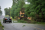 WATERBURY , CT-080420JS07—A driver maneuvers around a front loader cleating debris from a fallen tree on Oronoke Road in Waterbury as Tropical Storm Isaias tore through the region on Tuesday leaving a path of damage and many without power. <br /> Jim Shannon Republican-American