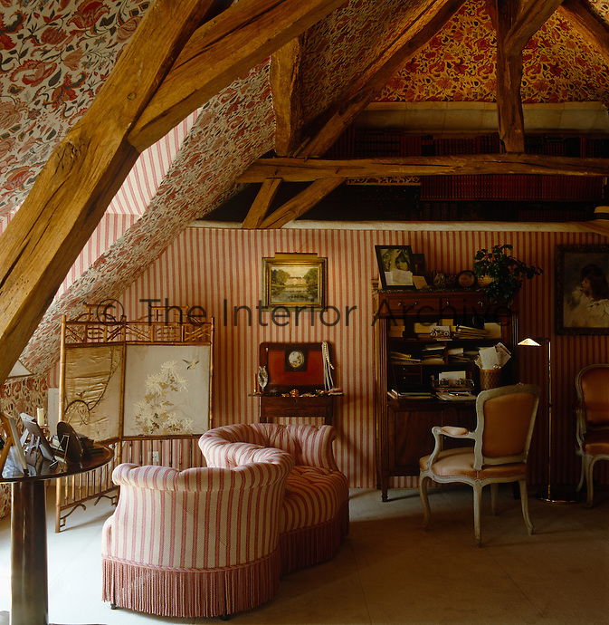 Striped fabric and patterned wallpaper covers the walls and ceiling of this attic bedroom