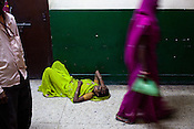 A tired patient is seen lying outside the doctors' clinic in Maharani Laxmibai Medical College in Jhansi, Uttar Pradesh, India. The Indian government spends $1.4 billion a year - on programs that include weighing newborn babies, counseling mothers on healthy eating and supplementing meals, but none of this is yeilding results. According to UNICEF, some 48% of Indian children, or 61 million kids, remain malnourished, the clinical condition of being so undernourished that their physical and mental growth are stunted. Photo: Sanjit Das/Panos for The Wall Street Journal.Slug: IMALNUT