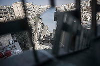 In this Sunday, Oct. 28, 2012 photo. A street of shattered buildings is viewed through a mirror used by rebel fighters to keep an eye over the enemy position at the Karmal Jabl battlefield in Aleppo, the Syrian's largest city. (AP Photo/Narciso Contreras).