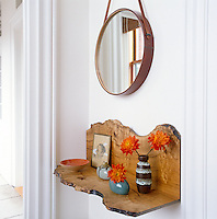 Under an oval mirror in the entrance hall a small shelf made of wood in a naturally curving organic shape displays a collection of ceramic vases and a small framed drawing