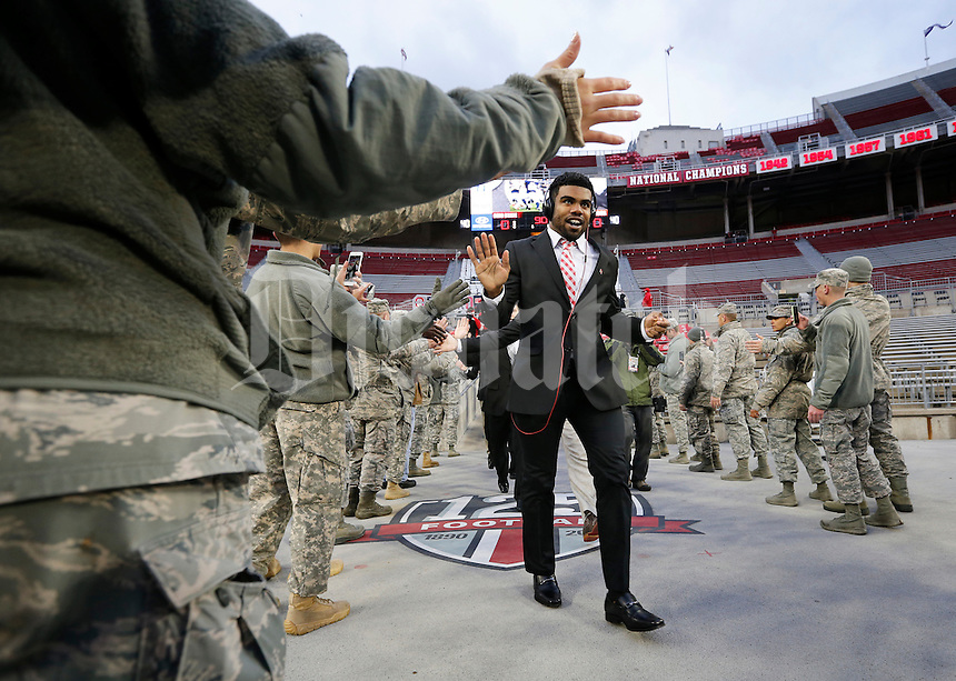 Ohio State Buckeyes running back Ezekiel Elliott high fives U.S. Army National Guard members while entering the stadium as part of Military Appreciation Night prior to the NCAA football game at Ohio Stadium on Nov. 1, 2014. (Adam Cairns / The Columbus Dispatch)
