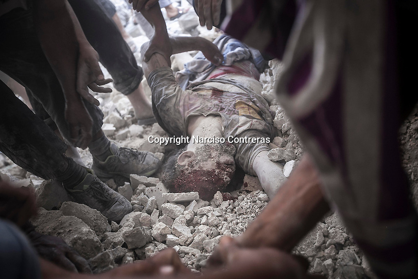 A dead body of a man is found among the debris of a demolished house building as Syrian civilians look for the victims of an aircraft shelling just some minutes after the house was targeted by one army plane at Tarik Albab neighborhood in the northeastern of Aleppo City. The Syrian army is carrying out aircraft shellings over residential areas throughout Aleppo City, killing hundreds of civilians in its attempt to sweep out the rebels.