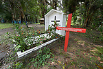 A red cross stands beside the grave in Anapu, Brazil, of Norte Dame de Namur Sister Dorothy Stang, a US nun who was assassinated in 2005. The red cross bears the names of 16 local rights activists who have been murdered since Stang's killing. Church activists say the killings continue, and they're about to erect a second red cross with even more names.
