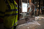"""© Joel Goodman - 07973 332324 . 26/03/2011 . London , UK . A policeman stands guard outside a branch of Santander bank , which has had its windows smashed with a chair . Hundreds of thousands of people attend an anti cuts demonstration under the banner """" March for the Alternative """" in central London , in protest at the coalition government's austerity measures . Photo credit : Joel Goodman"""