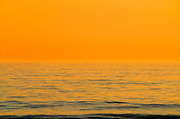orange and red sky over calm ocean water at sunset in the tropics