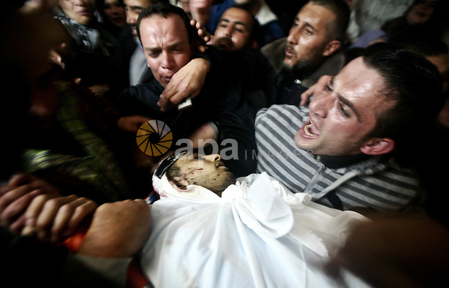 Palestinian relatives of Ahmed Salim, one of the Nasser Salah Addin Brigades who was killed in an Israeli air strike, mourn during his funeral in Gaza City,Sunday, March 11, 2012. Medics said Israeli air strikes on the Gaza Strip killed 18 Palestinians. Photo by Ali Jadallah
