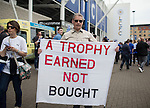 A Leicester fan with a trophy earned not bought banner during the Barclays Premier League match at the King Power Stadium.  Photo credit should read: David Klein/Sportimage