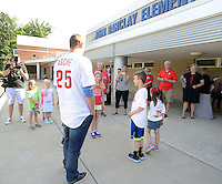 Phillies outfielder Cody Asche (left) arrives with Barclay Elementary School students Liam (center) and Katie Petersen (right) for a special assembly Wednesday June 17, 2015 in Warrington, Pennsylvania. Liam and Kate Petersen's parents won the unique experience through the Phillies Charities, Inc. Phantastic Auction. (Photo by William Thomas Cain)