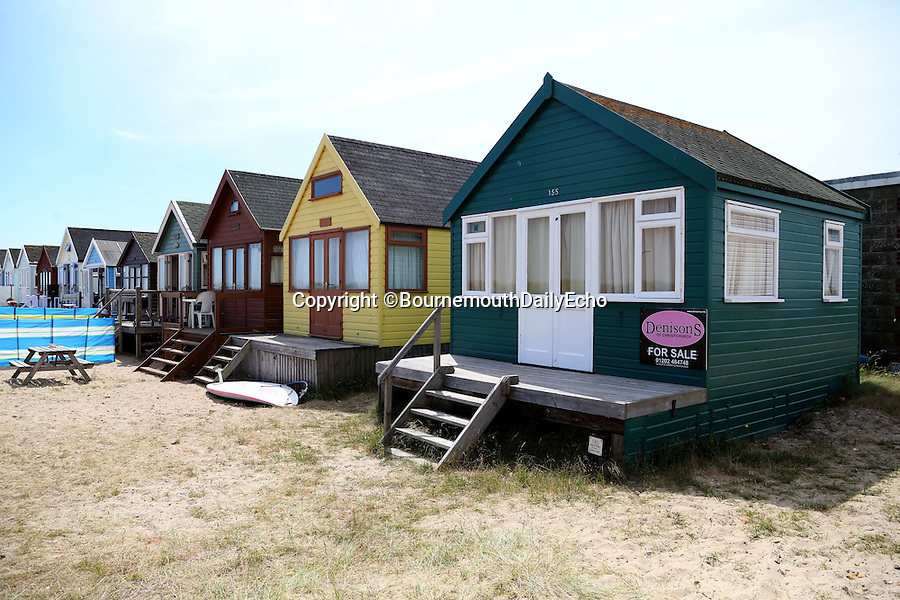 BNPS.co.uk (01202 558833)<br /> Pic: CorinMesser/BournemouthEcho/BNPS<br /> <br /> The beach hut sits at the end of the row at Mudeford Spit. <br /> <br /> Britain's most expensive beach hut has gone on the market for a whopping 225,000 pounds - and it doesn't even come with sea views.<br /> <br /> The wooden shack, that measures 13ft by 13ft, looks out onto sand dunes and offers  glimpses of the sea. It is also right next to a public toilet block.<br /> <br /> The timber hut on Mudeford Spit near Christchurch, Dorset, is divided up into three rooms - a living area, bedroom and a mezzanine level.<br /> <br /> It has no bathroom, mains electricity or running water and requires a ride on a novelty land train or a 30 minute walk to get there.