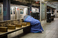 Un-domiciled individual escapes the cold on a subway platform  in New York on Friday, March 28, 2014. (© Richard B. Levine)