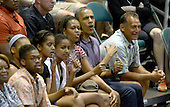 President Barack Obama reacts to a play as he, first lady Michelle Obama and daughters Malia Obama and Sasha Obama attend the Hawaiian Airlines Diamond Head Classic men's basketball game between the Oregon State Beavers and the University of Akron Zips at the University of Hawaii at Manoa Stan Sheriff Center, Sunday, December 22, 2013. The first lady's brother, Craig Robinson, is the Oregon State University Men's Head Basketball Coach.  At far right is Bobby Titcomb, one of the President's oldest friends.<br /> Credit: Cory Lum / Pool via CNP