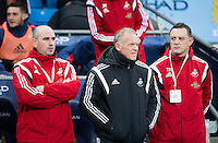 Swansea City Caretaker Manager Alan Curtis stands in the dugout with Performance Psychologist Ian Mitchell, left and Goalkeeping Coach Tony Roberts, right, during the Barclays Premier League Match between Manchester City and Swansea City played at the Etihad Stadium, Manchester on 12th December 2015