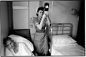 A nurse adjusts a drip by a patient's bedside at Mayday Hospital, Thornton Heath