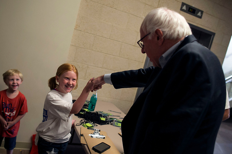 """UNITED STATES - August 16: Sen. Bernie Sanders, D-Vt., greets a young fan as he arrives to speak at the Loras College Athletic and Wellness Center in Dubuque, Iowa, on Sunday, August 16, 2015. The """"town meeting,"""" was the fourth campaign event of the day for Sanders. (Photo By Al Drago/CQ Roll Call)"""